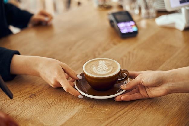 Женщина-бариста дает заказ клиенту в модном кафе. чашка кофе с латте арт.