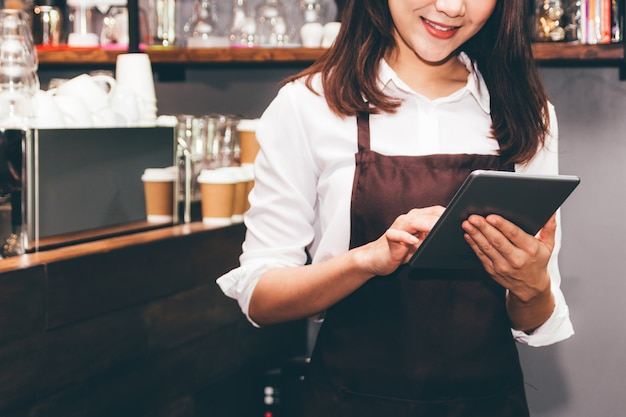 Barista woman using digital tablet compute in coffee shop counter bar