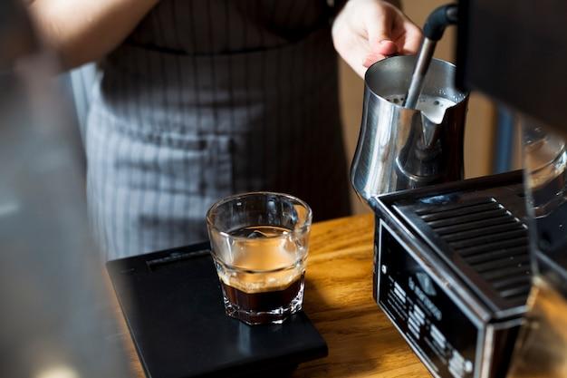 Рука barista на пару для приготовления латте кофе в кафе