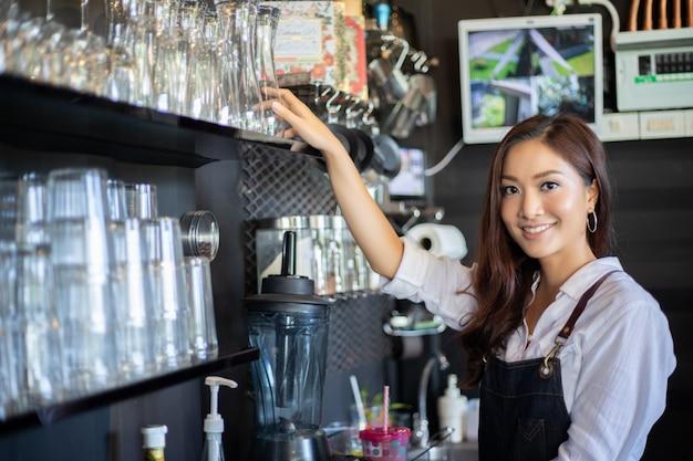 Азиатские женщины barista, улыбающиеся и использующие кофемашину в прилавке кафе - работница, владелец малого бизнеса, еда и напитки, кафе