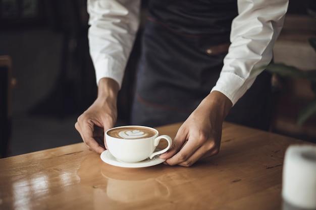 Мужской barista подготавливая кофе для клиента в кофейне. владелец кафе обслуживает клиента в кафе.