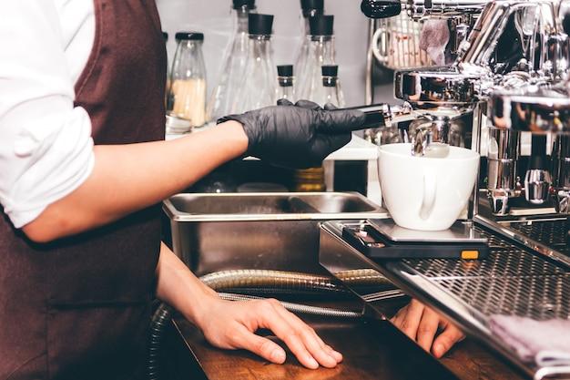 Женщины barista используют кофемашину для приготовления кофе в кафе