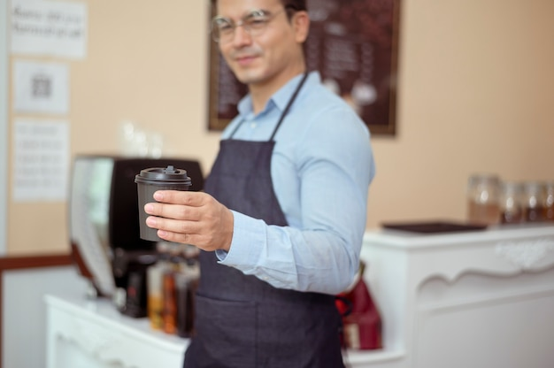 Бариста вручают чашку горячего кофе и выпечку, чтобы предложить покупателю в кафе