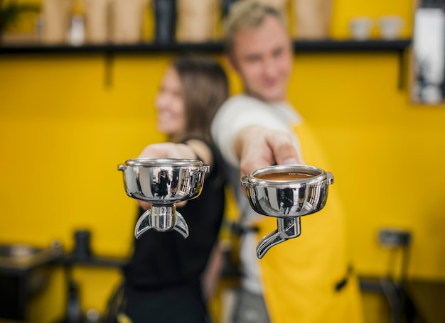 Baristas posing back to back while holding cups