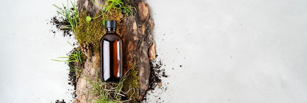 Bark tree, tiny mosses and grass of organic cosmetic products in glass brown bottle
