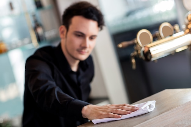 Barkeeper cleaning counter with napkin