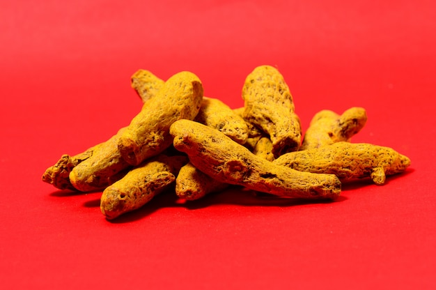 Barks of yellow turmeric on red space
