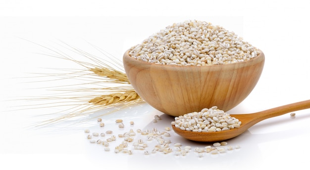Barley grains in the wood bowl isolated