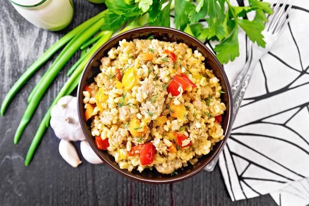 ひき肉、黄色と赤のピーマン、ニンニクと玉ねぎを粘土のボウルに入れた大麦のお粥、上から木の板の背景にタオルとパセリ