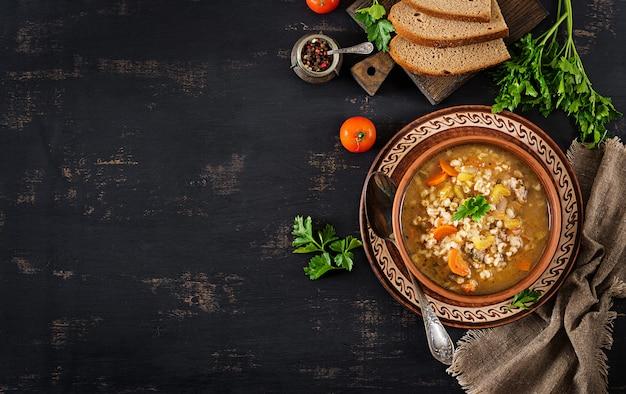 Ячменный суп с морковью, помидорами, сельдереем и мясом на темном фоне. вид сверху.
