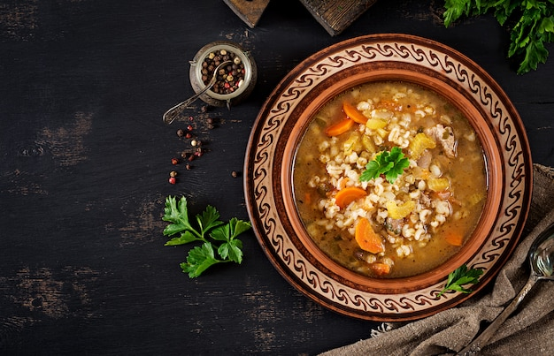 Barley soup with carrots, tomato, celery and meat on a dark background