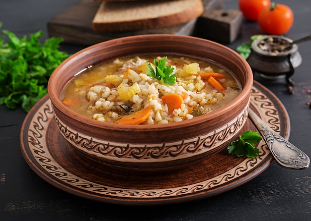 Barley soup with carrots, tomato, celery and meat on a dark surface