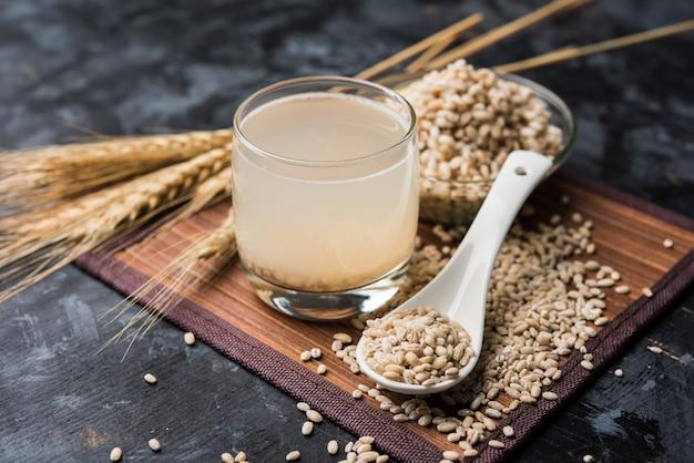 원시 및 조리된 진주 보리 밀 또는 씨앗이 든 유리잔에 보리 물. 선택적 초점