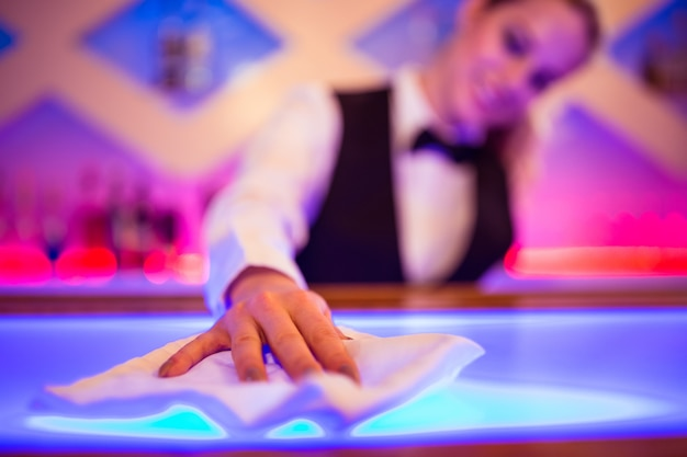 Barmaid cleaning counter with napkin