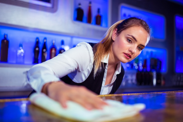 Barmaid cleaning counter