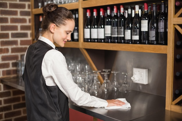 Barmaid cleaning table