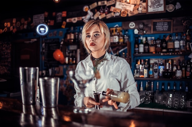 Barmaid formulates a cocktail on the taproom