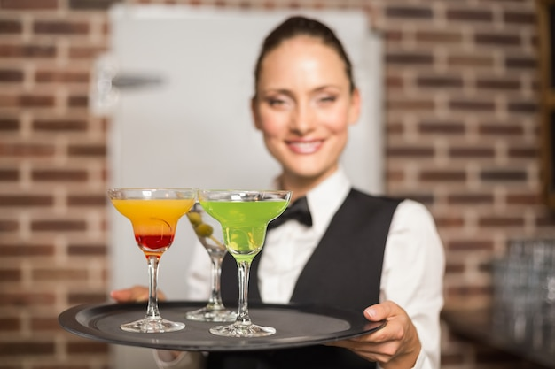 Barmaid holding plate with cocktails