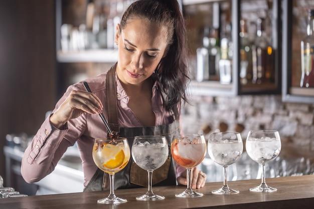바메이드는 바에서 5가지의 다양한 진토닉 음료를 준비하고 있습니다.