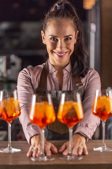 Barmaid는 카메라를 보며 웃고 있는 바에서 aperol spritz 칵테일을 제공합니다.