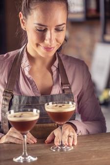 Barmaid는 바에서 에스프레소 마티니 커피 칵테일 2잔을 제공합니다.