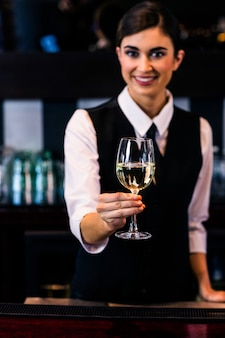 Barmaid serving a glass of wine in a bar