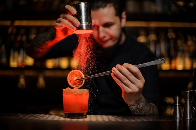 Barman adding to an alcoholic cocktail in the glass a dried orange with tweezers and aromatic powder in the red light on the bar counter