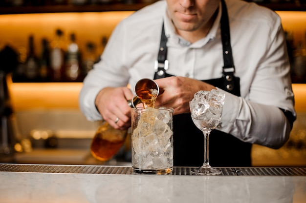 Barman adding alcoholic drink into a glass filled with ice cubes