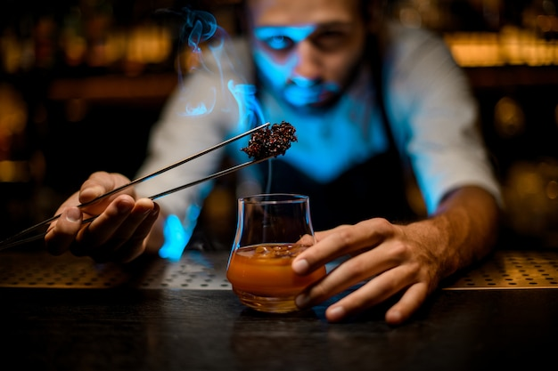 Barman adding chilled melting caramel with twezzers to the cocktail glass with ice cubes under blue lights
