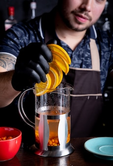 Barman adds sliced orange to tea close-up