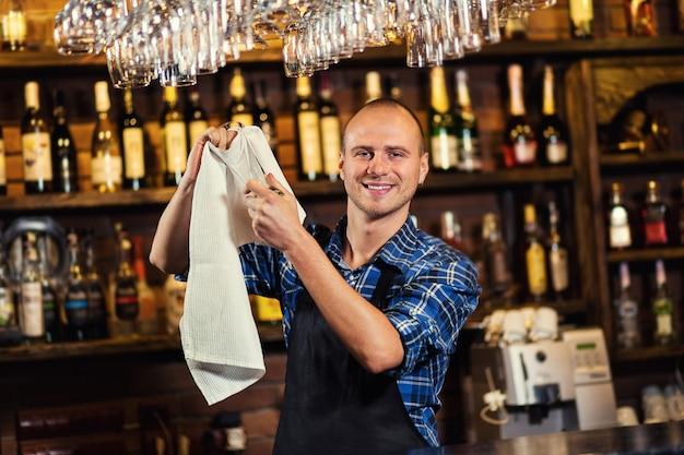 Бармен за работой в пабе, портрет веселого бармена, стоящего работника, официант, дающий меню, паб. бар. ресторан. классический. вечер. европейский ресторан. европейский бар. американский ресторан. американский бар.