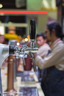 Barman or bartender pouring a draught lager beer from beer tap on counter