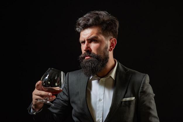 Barman or bartender serves cognac retro vintage man with cognac or scotch sommelier man confident we...