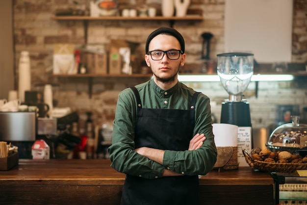 Barman in black apron standing against bar counter.