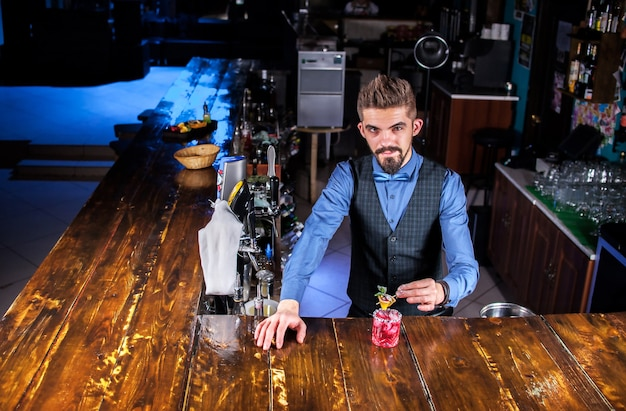 Barman concocts a cocktail behind the bar