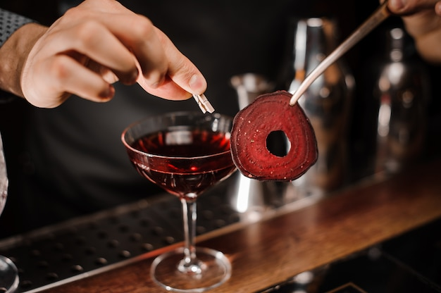 Barman decorating a red cocktail drink with a slice of a beet