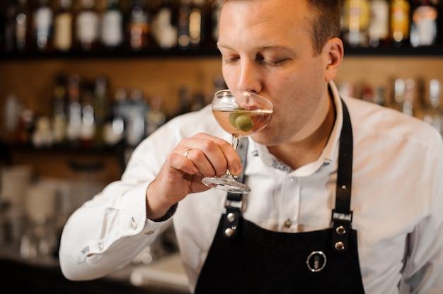 Barman drinking alcoholic cocktail with green olives