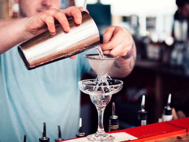 Barman filling cocktail glass with alcohol beverage