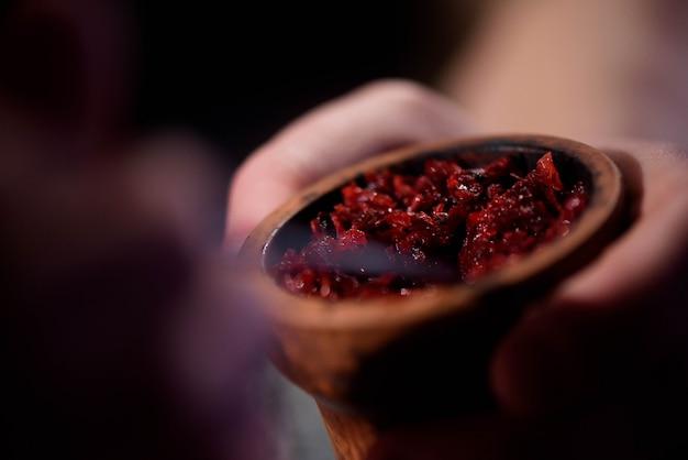 Barman fills black burnt ceramic bowl for hookah smoking different types of tobacco.