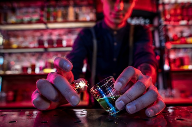 Barman finishes preparation of alcoholic cocktail, sets fire to drink in multicolored neon light, focus on glass
