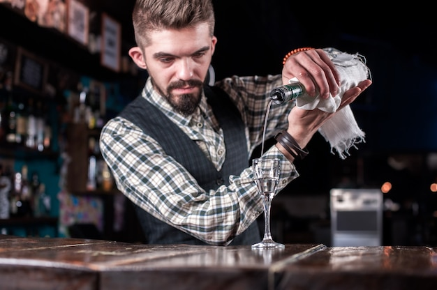 Бармен готовит коктейль в баре