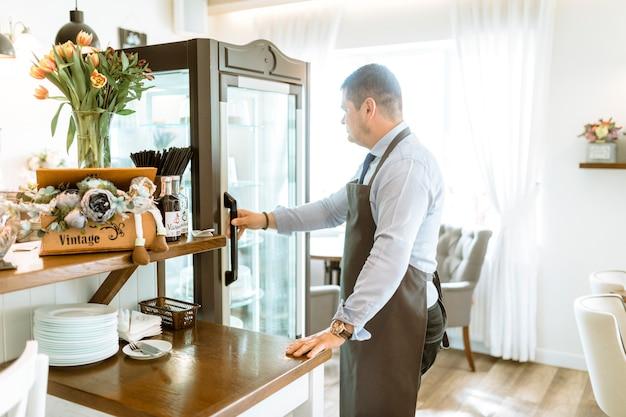 Barman in front of fridge
