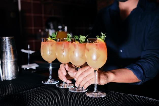 バーマンはナイトクラブのクライアントにオレンジ色の飲み物のグラスを与えます。カクテルを準備するバーテンダーのクロップドショット。