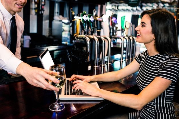 Barman giving a glass of wine at woman using laptop in a bar