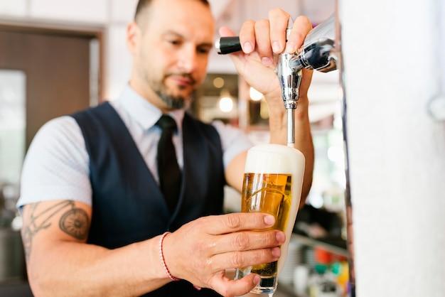 Бармен рука у крана разливает разливное светлое пиво в пабе