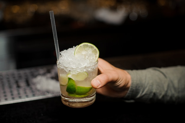 Barman hand holding a glass filled with caipirinha cocktail with a straw