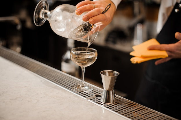 Barman hand pouring alcoholic drink mixed with ice into a glass