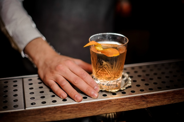 Barman hand with a glass of fresh old fashioned cocktail with orange peel
