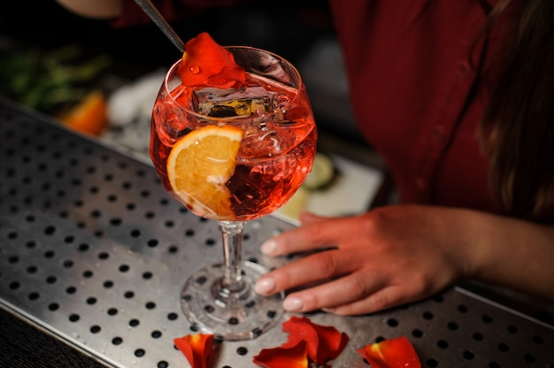 Barman hands decorating a glass of aperol syringe cocktail with rose petals