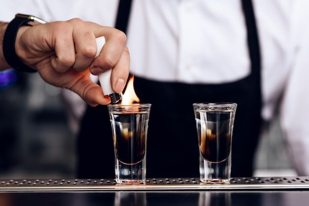 The barman has prepared cocktails for customers in the bar.